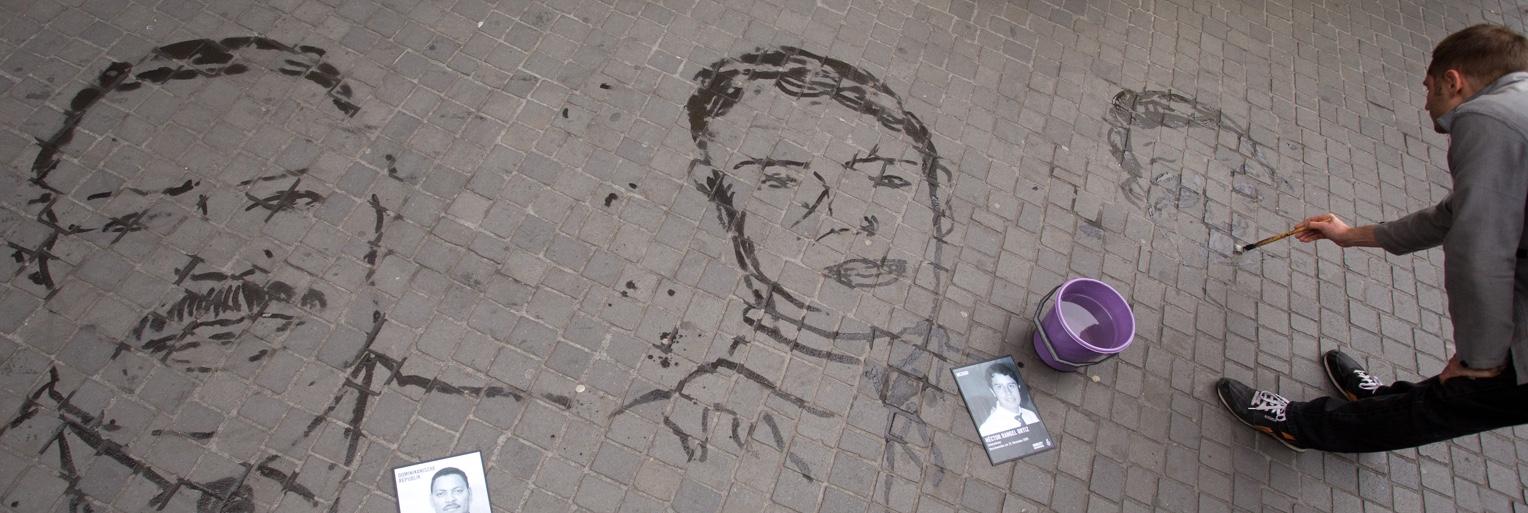 Amnesty International - Fading Portraits - Mahler mahlt mit Wasser Gesischten auf dem Boden - Headerbild